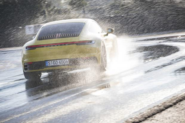 Yellow Porsche 911 seen from behind in the wet