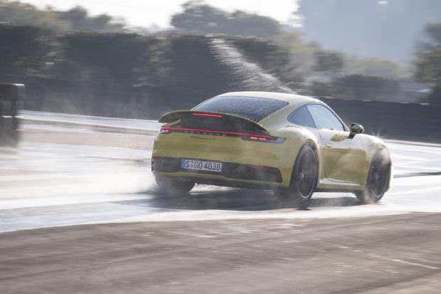 Yellow Porsche 911 driving in the wet